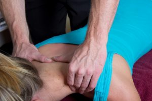 A chiropractor gently manipulating the neck